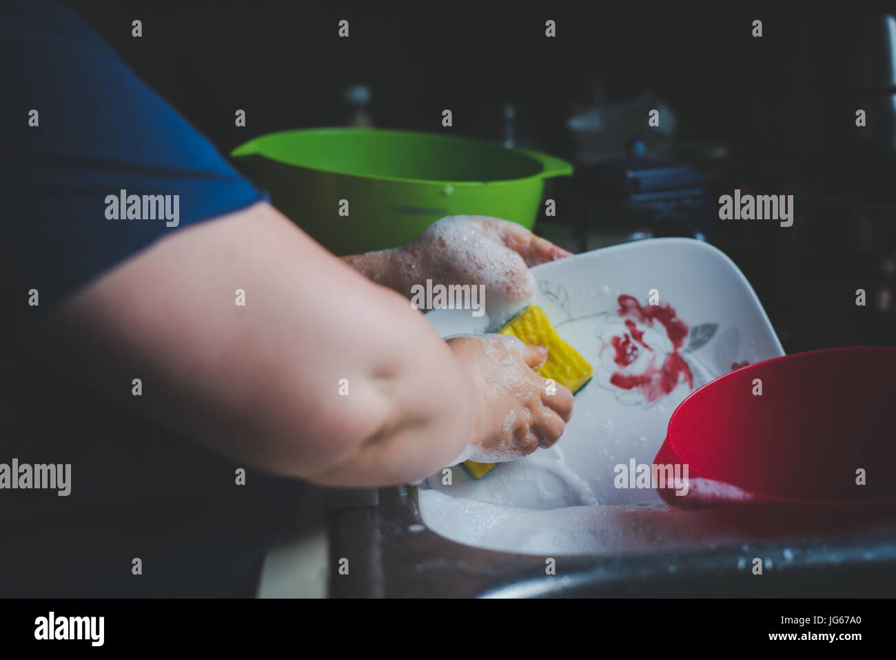 A woman washing dishes at a sink. - Stock Image