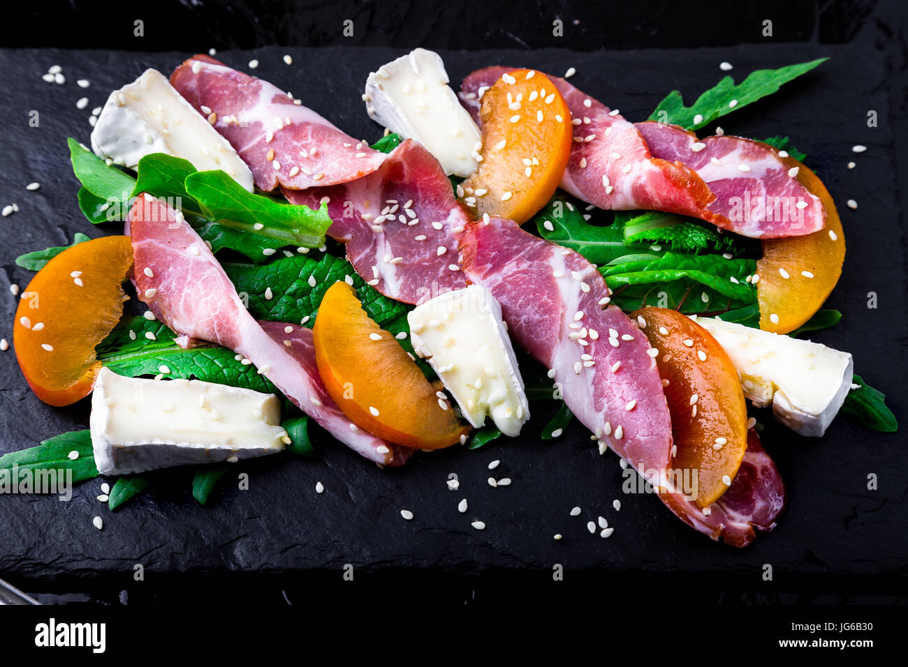 Salad with ham jamon serrano, camembert, melon, arugula on black stone slate plate on black background. Top view. - Stock Image