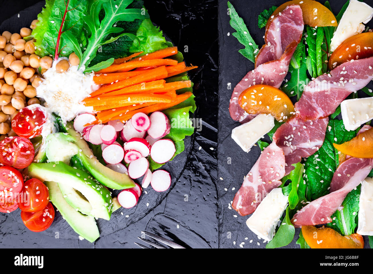 Two different salads om black stone slate. Vegan salad. Meat salad. Salad with ham jamon serrano, camembert, melon, - Stock Image
