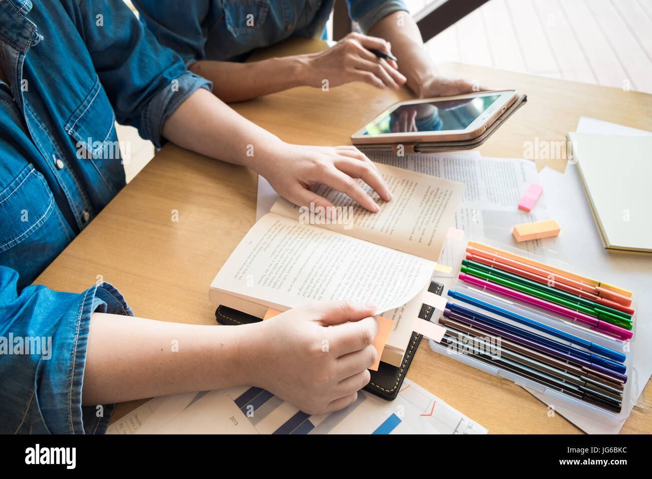 Young woman and man studying for a test/ an exam. Tutor books with friends - Stock Image