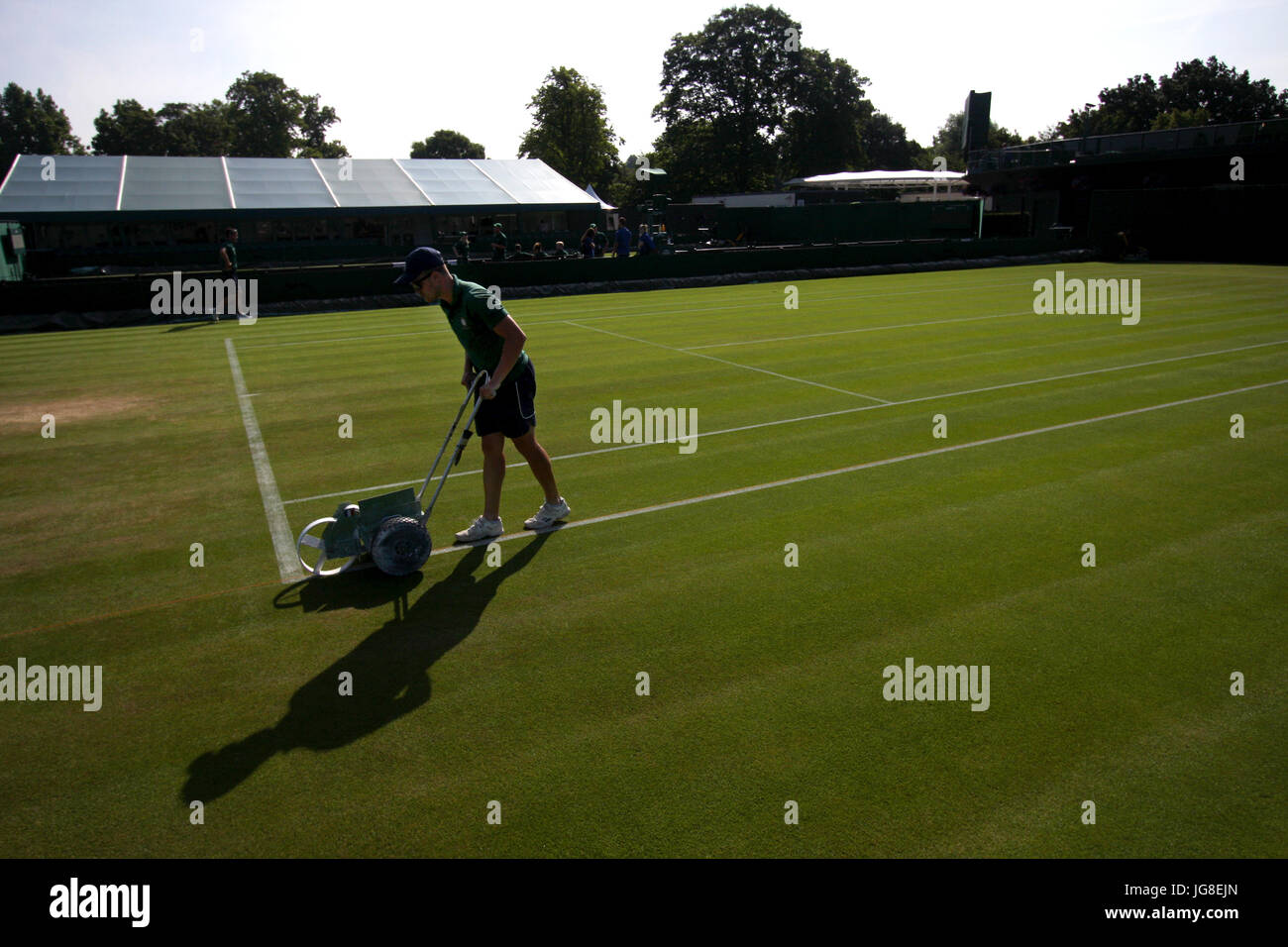 London, UK. 04th July, 2017. A bellboy chalks the line of one of the outside courts at the All England Lawn Tennis - Stock Image
