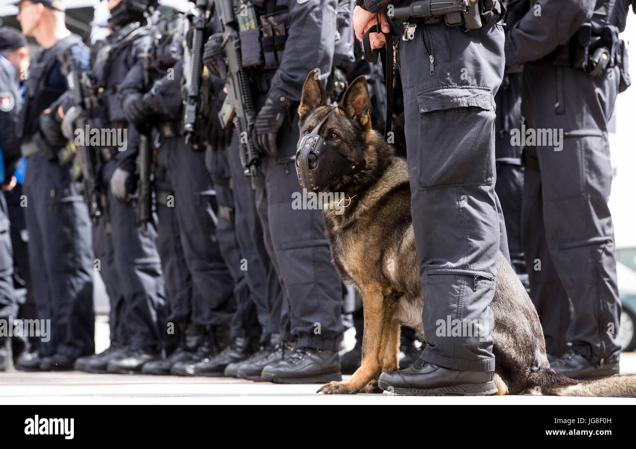 dpatop - A police dog sits in between officers of the special unit 'BFE ' (Beweissicherungs- und Festnahmeeinheit) Stock Photo