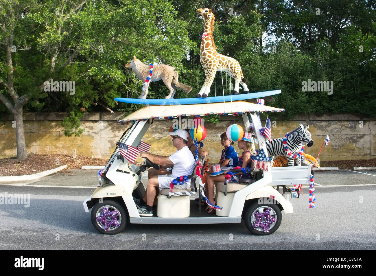 Sullivan's Island, South Carolina, USA. 4th July, 2017. A family rides along in a golf cart decorated with stuffed - Stock Image