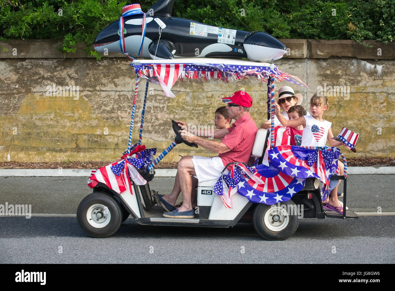 Sullivan's Island, South Carolina, USA. 4th July, 2017. A family rides along in a golf cart decorated in patriotic - Stock Image