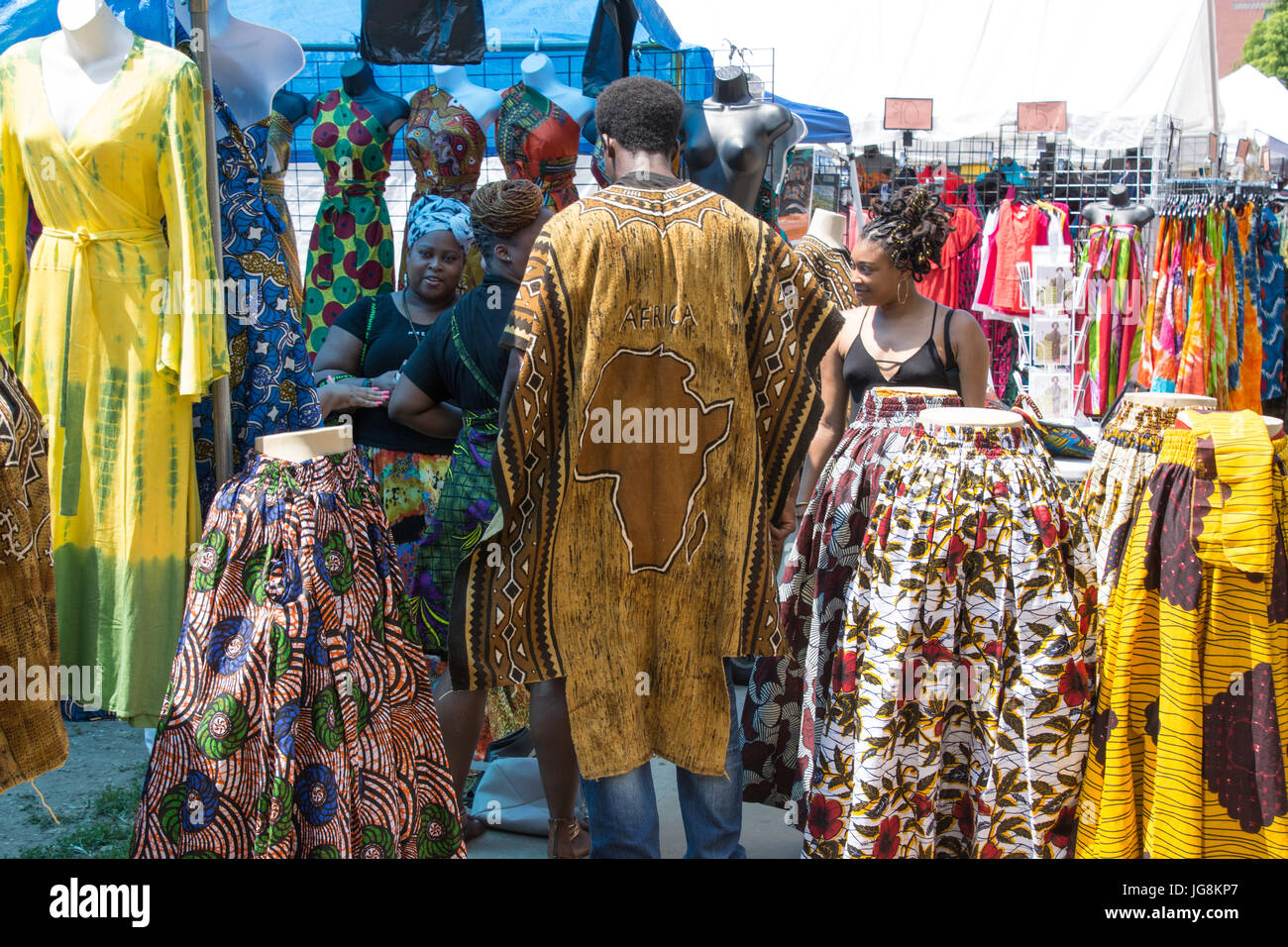 Brooklyn, USA. 4th July, 2017. A clothing vendor displays an Africa map on his back as he tends to customers. Brooklyn's - Stock Image