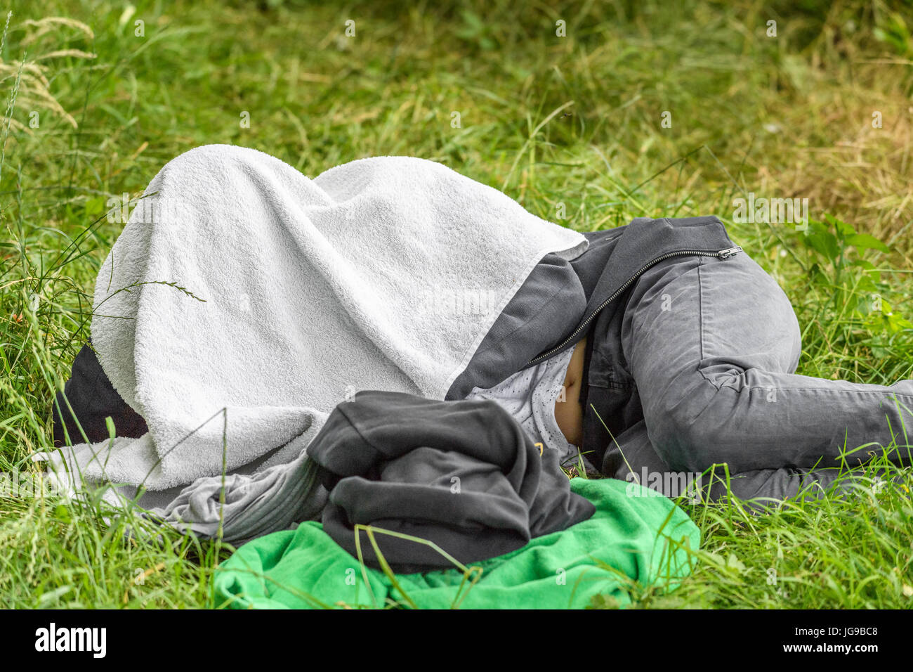 Boy hides his head under a towel either to shut himself off from others or to have a  quiet snooze. - Stock Image