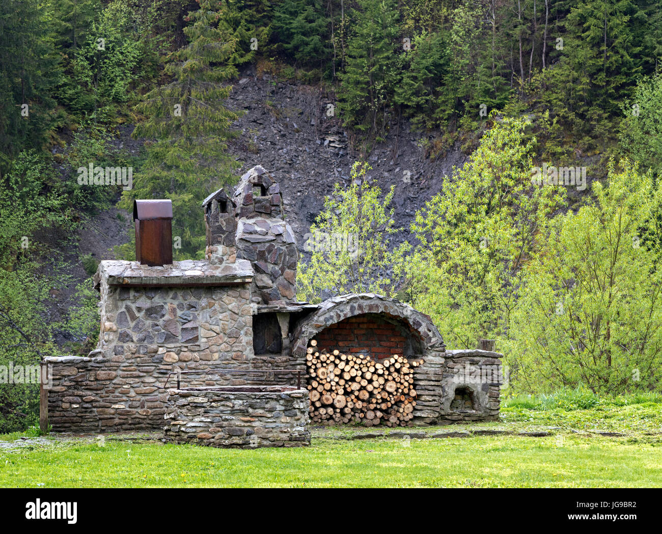 An old stone stove with firewood, a skewer for meat and a smokehouse for cooking outdoors in the Carpathians. - Stock Image