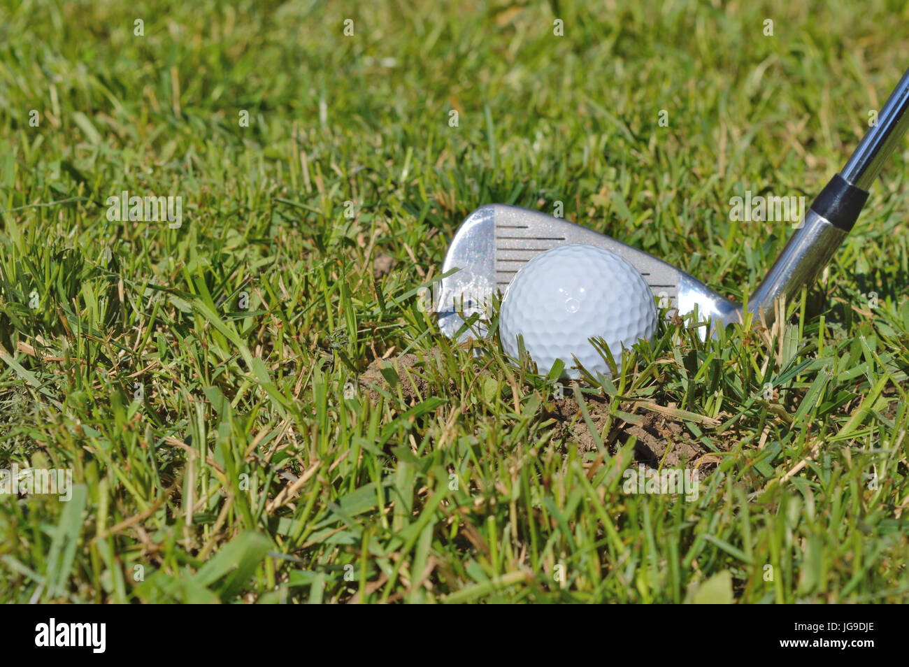 Golfer hitting a ball off the fairway - Stock Image