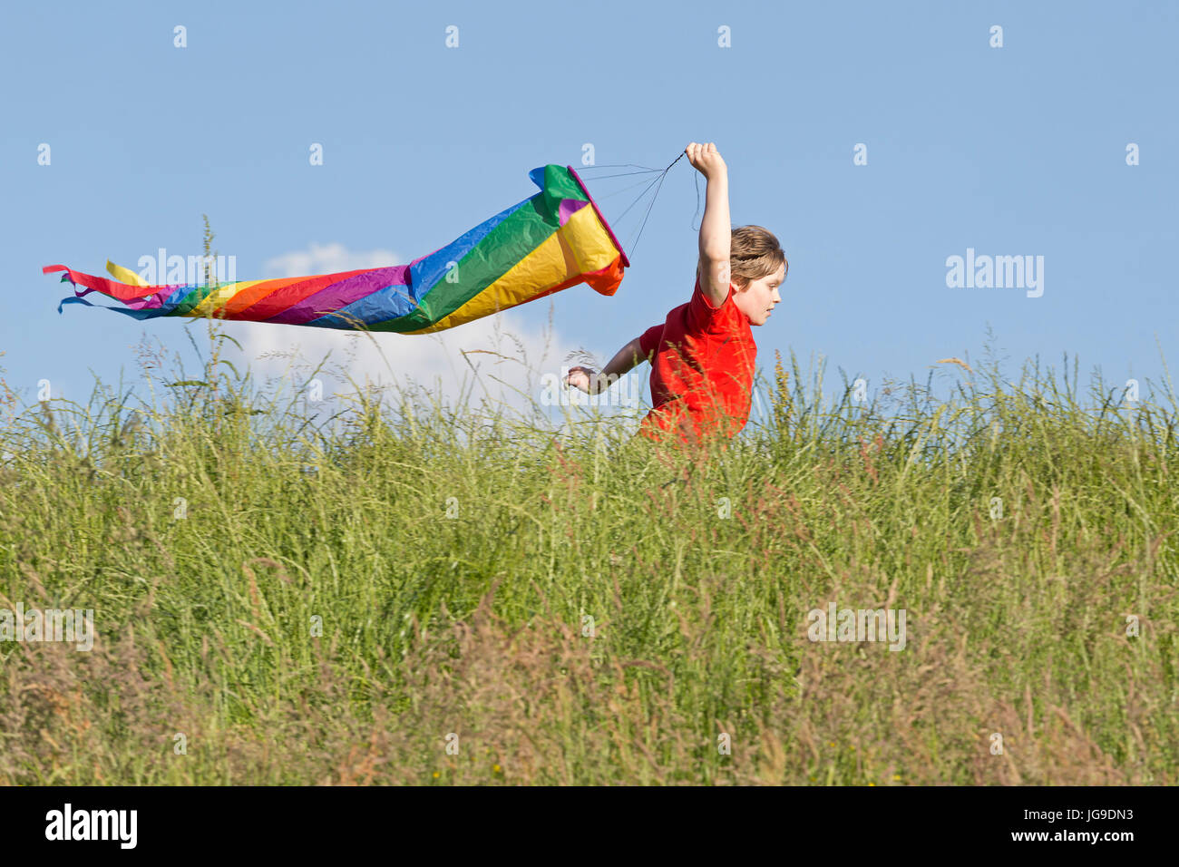 young boy running with wind sleeve, Bleckede, Lower Saxony, Germany - Stock Image