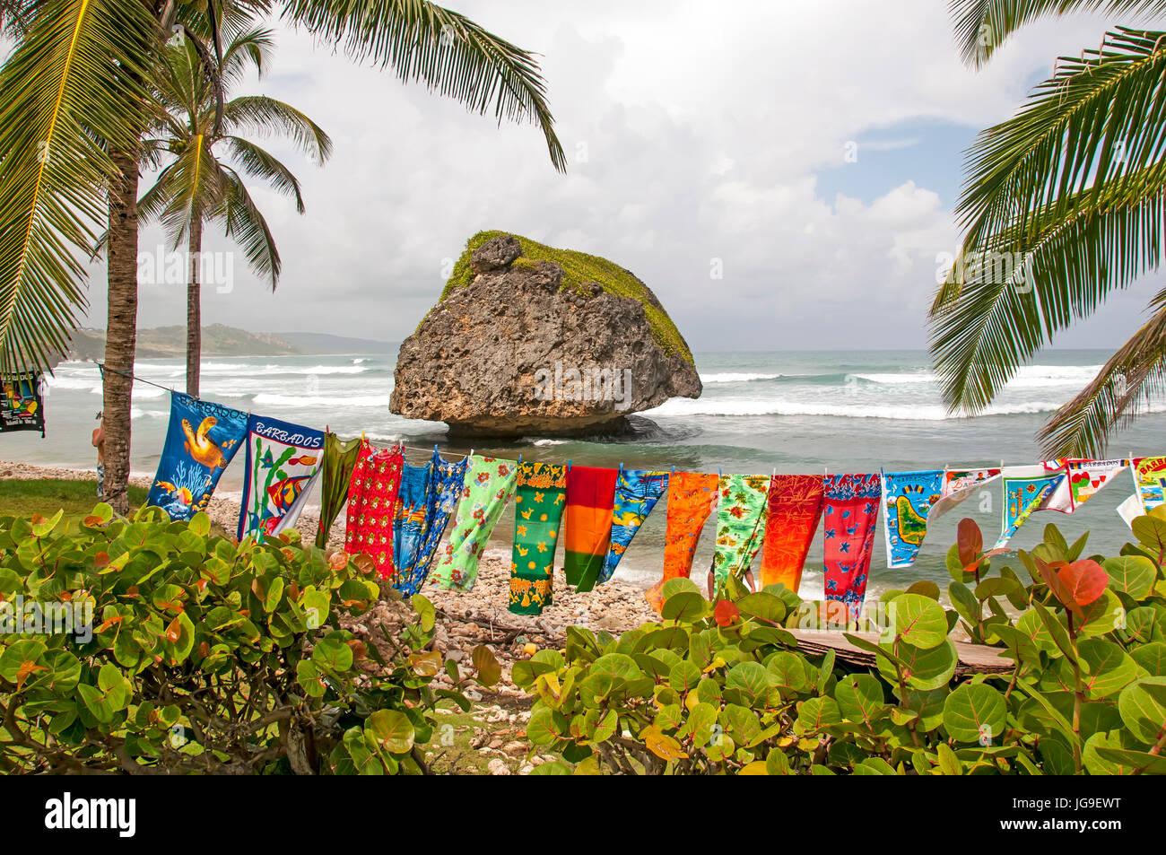 Bathsheba Barbados dramatic boulder on deserted beach with colorful clothes on clothesline blowing in wind. - Stock Image