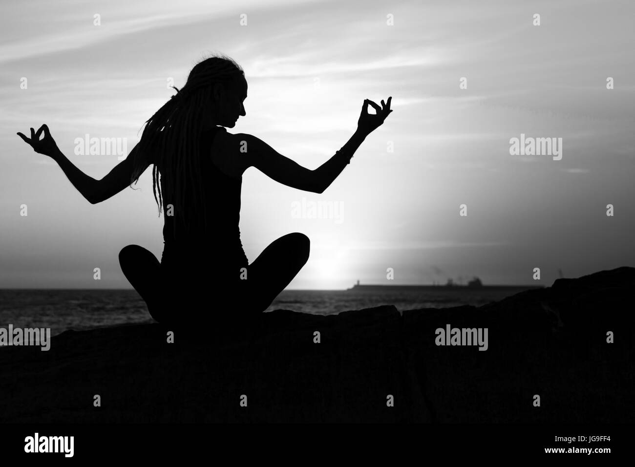 Black and white silhouette of yoga woman meditation on the sea beach
