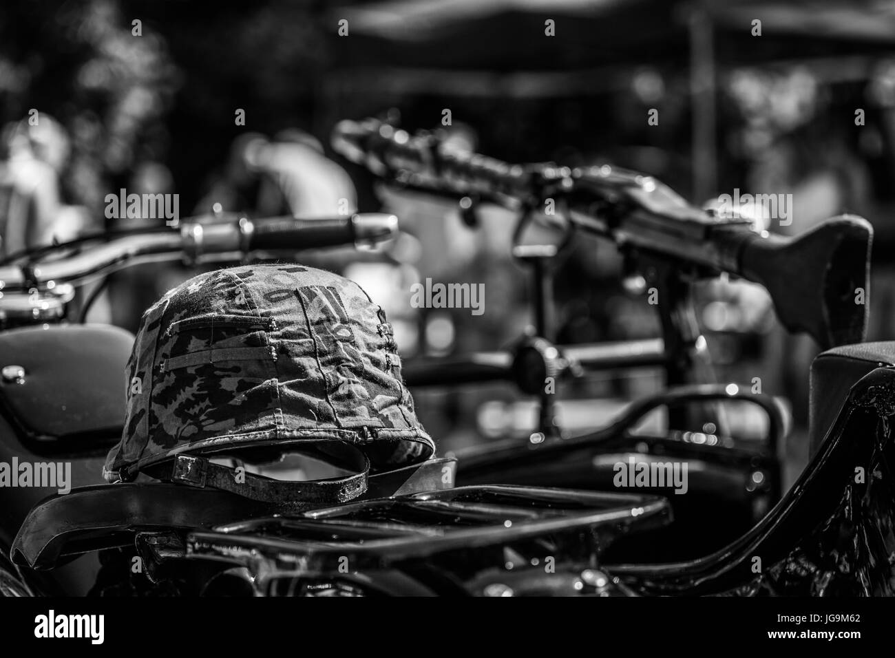 Military cap lying on BMW R71 old motorcycle after renovation with a rifle (toy) in the background. Black and white. - Stock Image