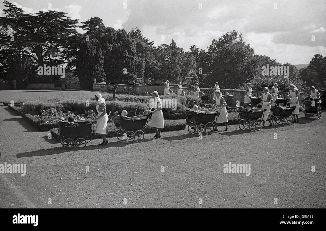 1940, England, Essex, group of nurses and chrome wheeled prams in the grounds of Stanstead Hall, home of Sydney - Stock Image