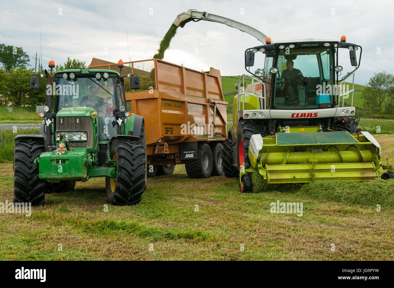 Silage lifting with John Deere tractor and CLAAS Chopper, South west Scotland. Galloway - Stock Image