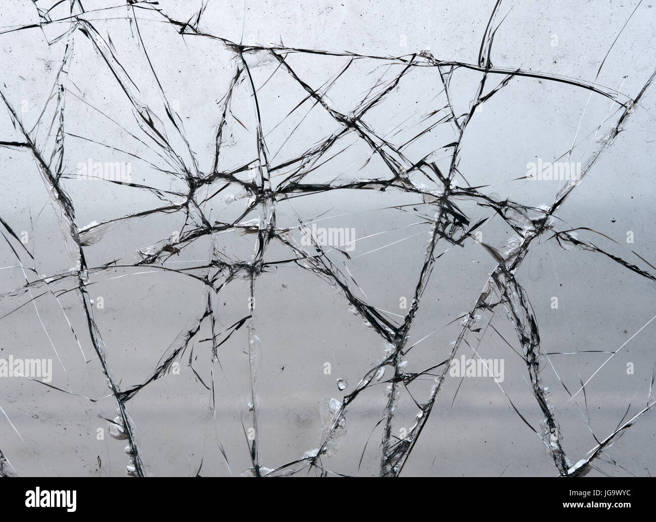 Shattered broken glass pattern window pane close up - Stock Image