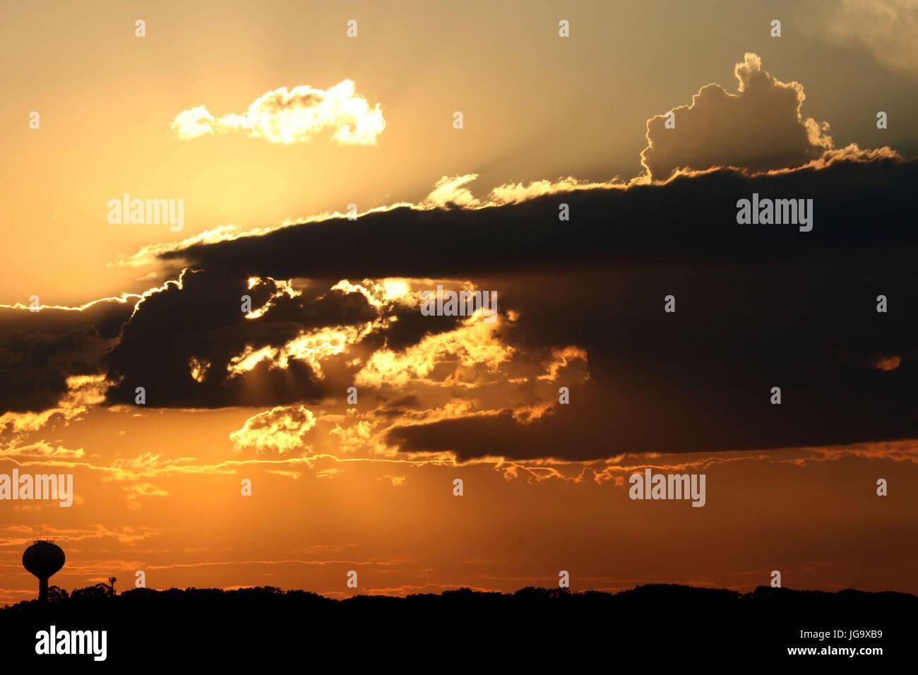 Sun peeks thru clouds during sundown with water tower - Stock Image
