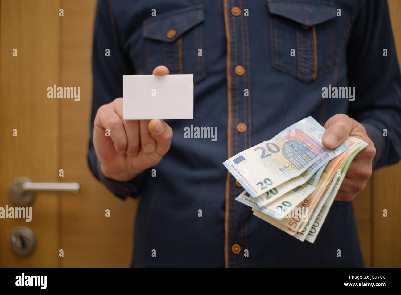 Businessman holding a bank card, and in the other hand holding the money in cash, finance, businessman - Stock Image