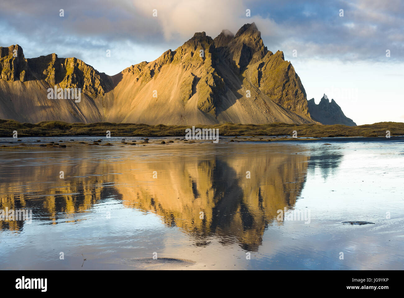 Stokksnes and Vestrahorn mountains in late afternoon light reflected in shallow water, Iceland Stock Photo