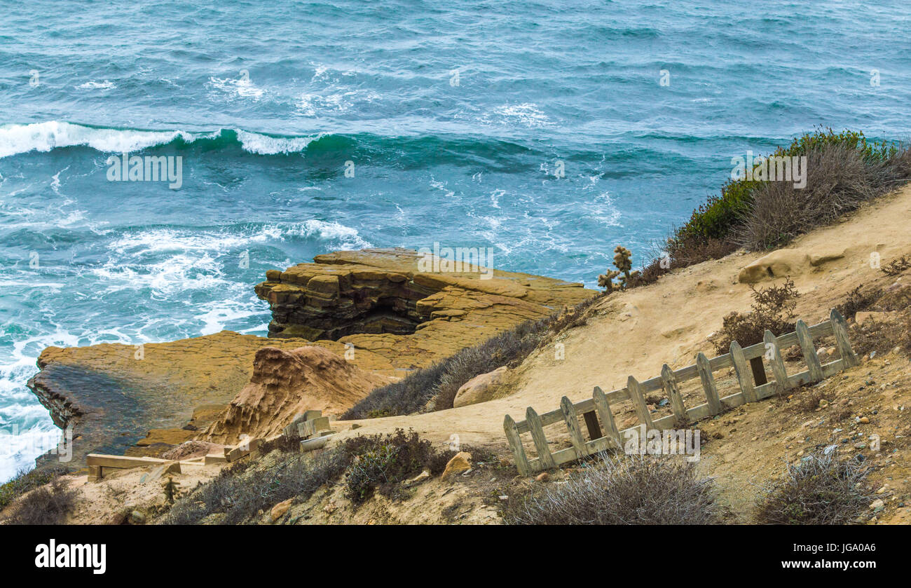 rocky shale cliffs with weathered fence on Pacific Ocean in San Diego, California Stock Photo
