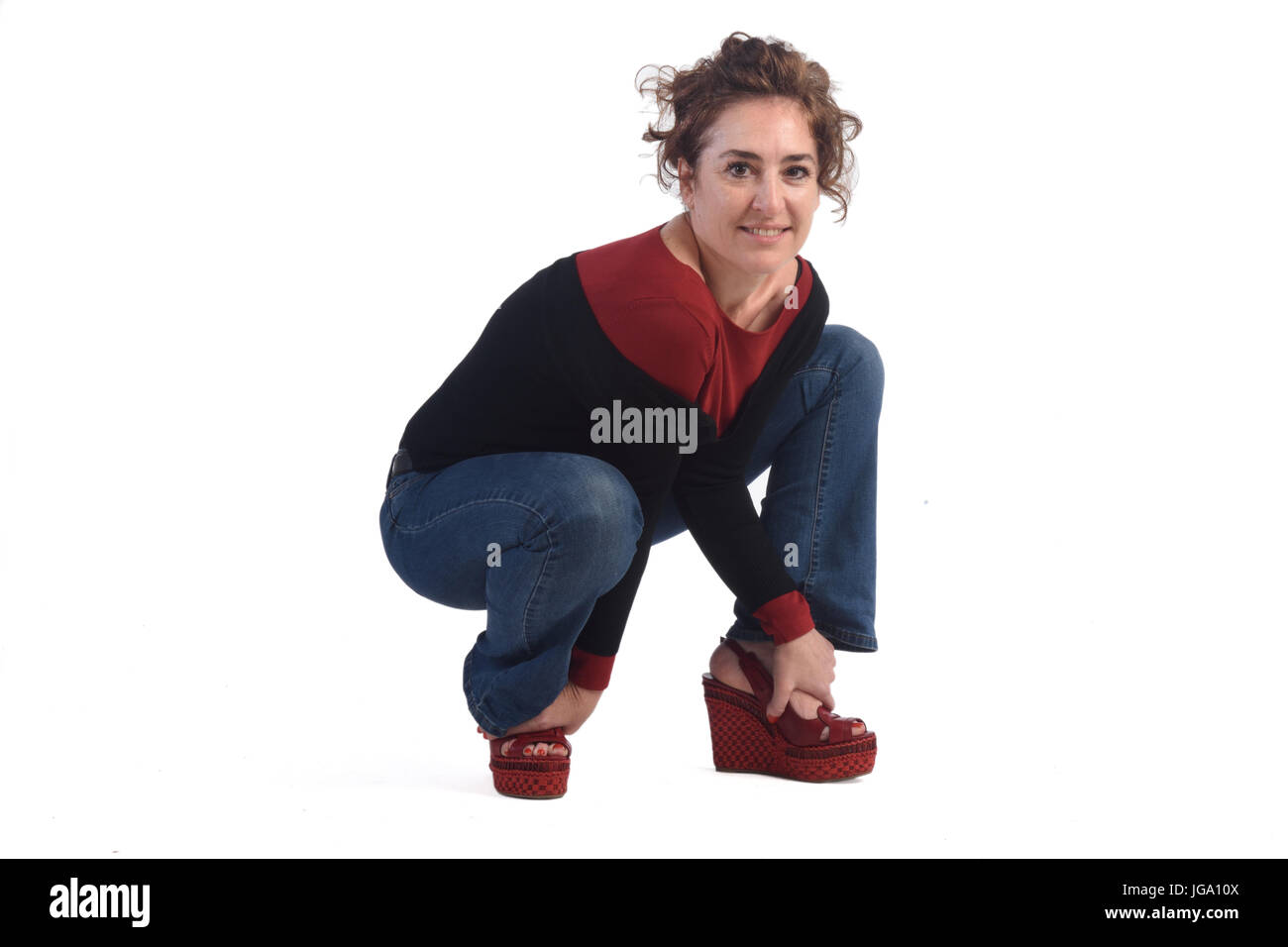 Woman crouching on a white background - Stock Image