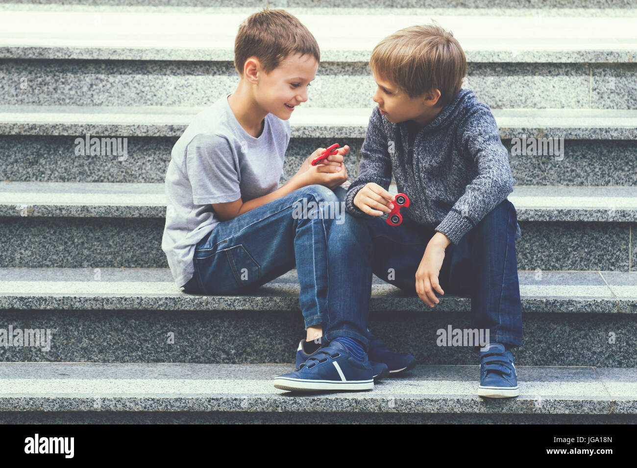 Boys playing with a fidget spinners outdoors - Stock Image
