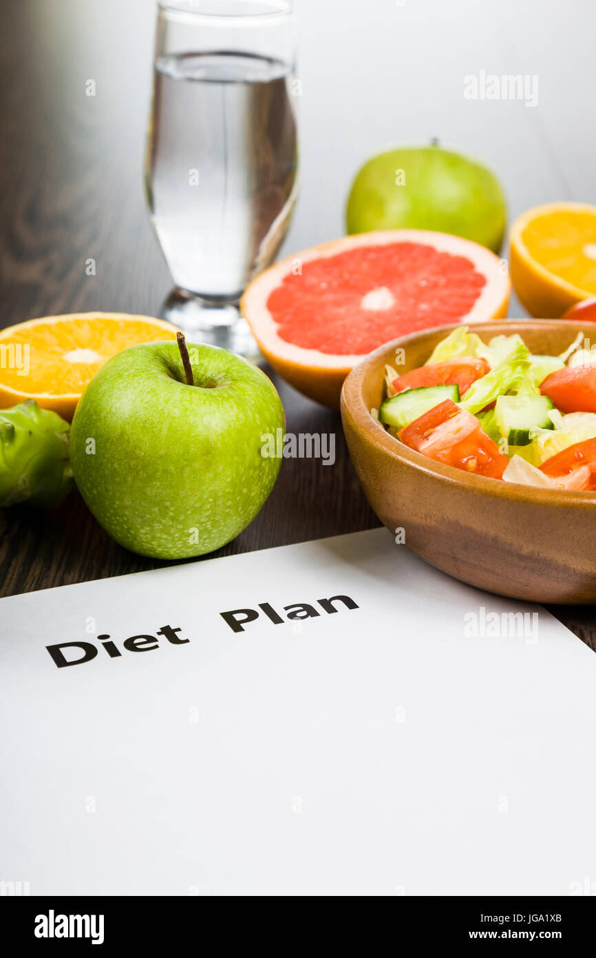 Food and sheet of paper with a diet plan on a dark wooden table. Concept of diet and healthy lifestyle. - Stock Image