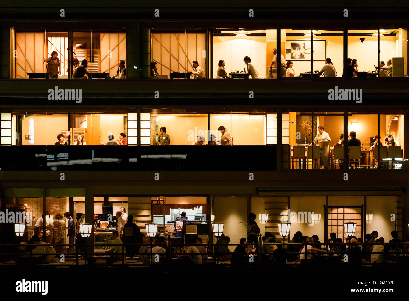 Multi-layered restaurant on the banks of The Kamo River (Kamo-gawa), with people dining, in traditional clothing, - Stock Image