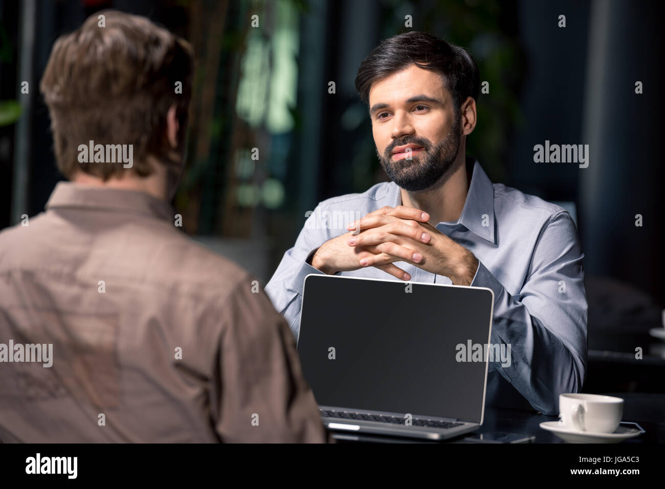 business team on meeting discussing project with laptop in cafe, business lunch concept - Stock Image