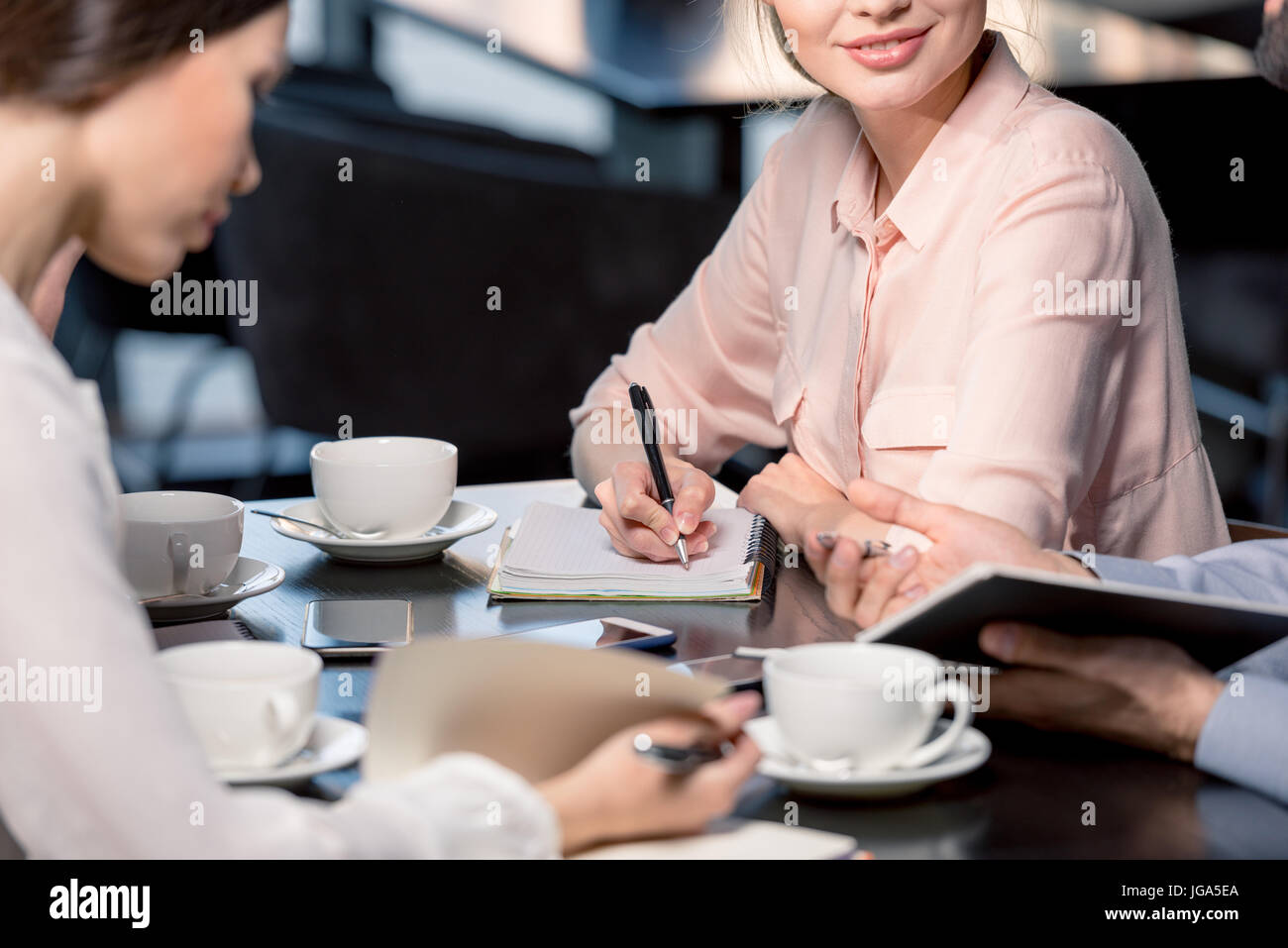 Cropped shot of young people discussing project during business meeting in cafe, business lunch concept - Stock Image