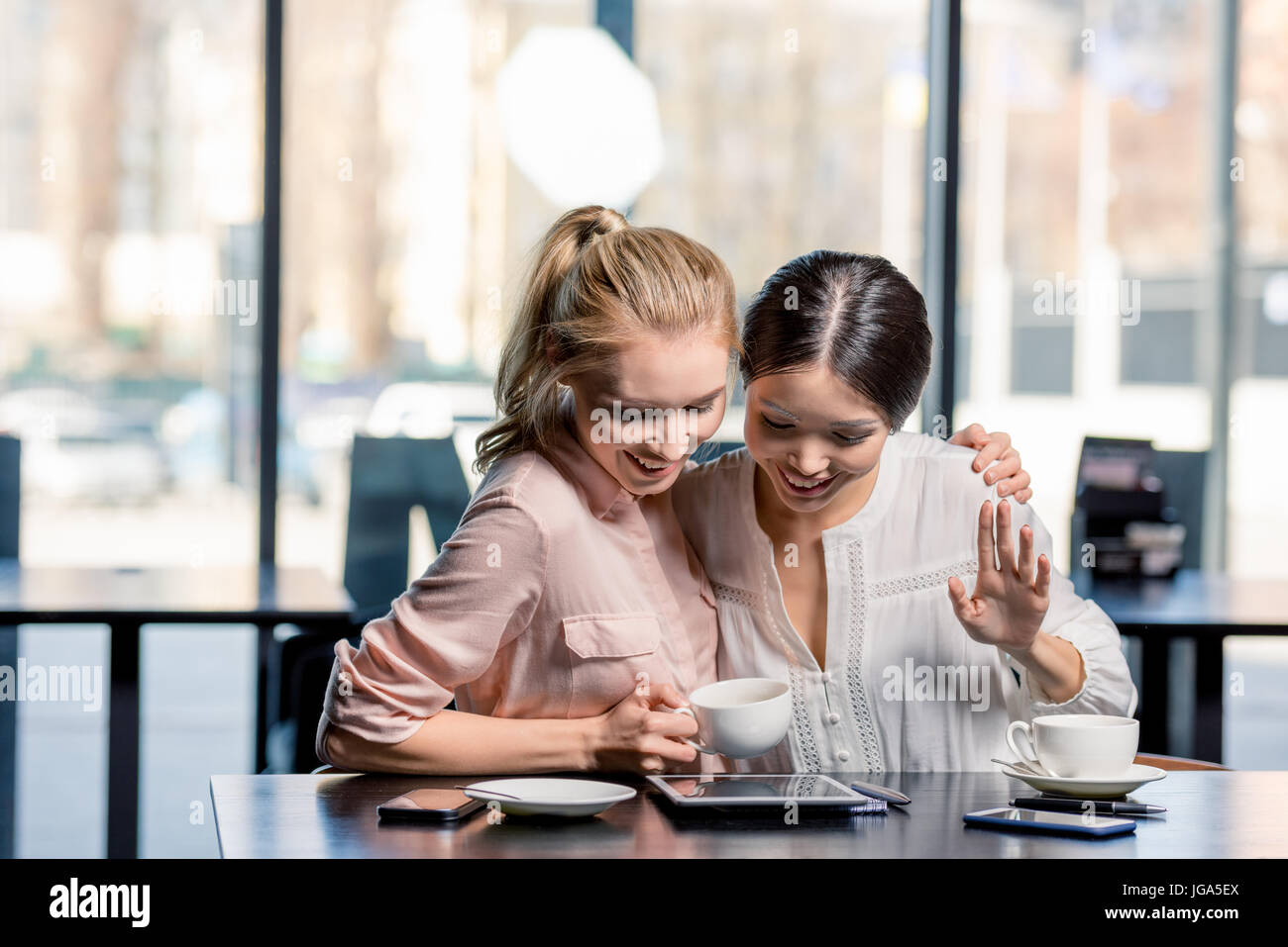 Smiling young women using digital tablet while drinking coffee in cafe, lunch meeting concept - Stock Image