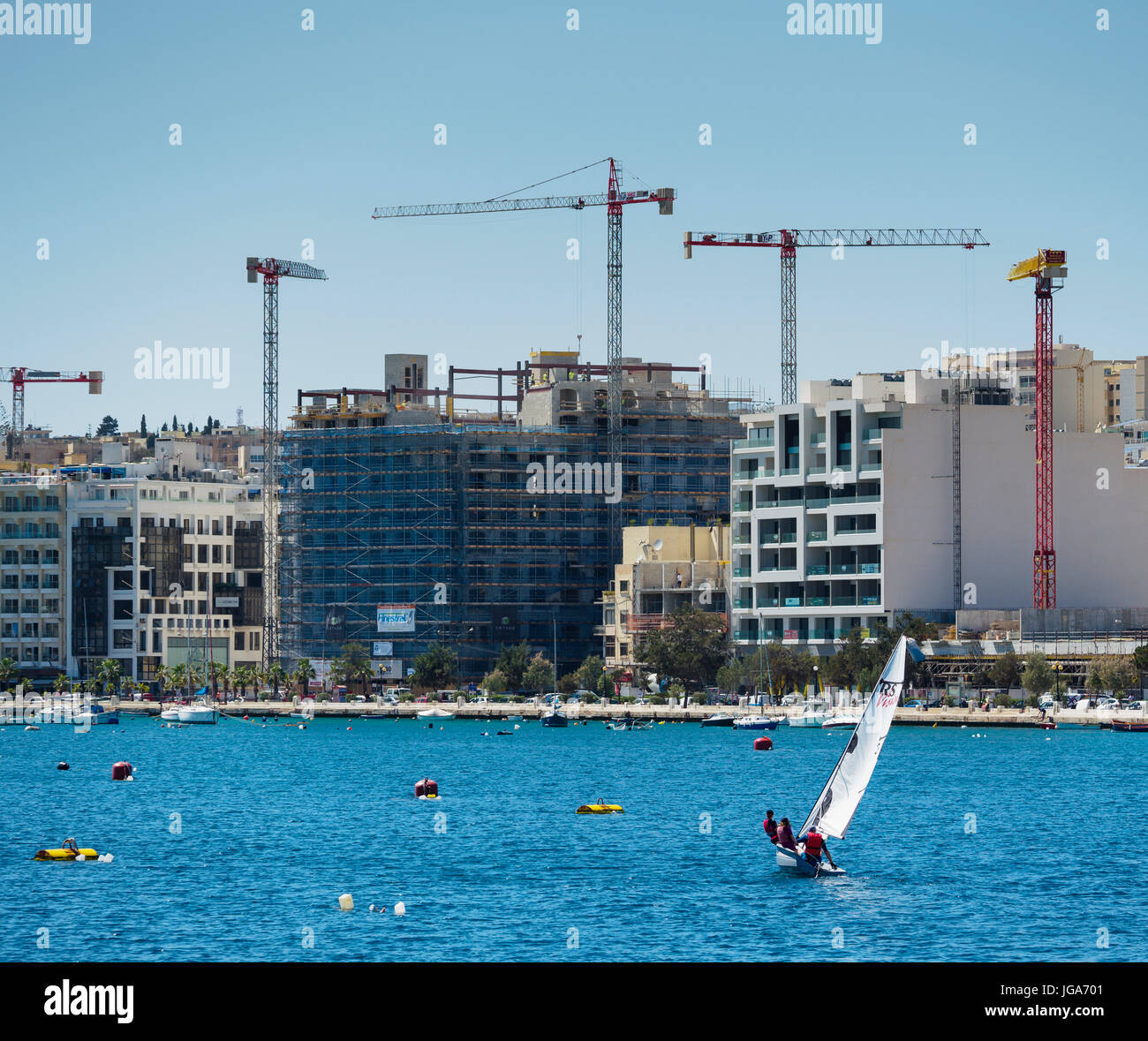 Five building cranes stand at the waterside promenade of Sliema / Malta. - Stock Image