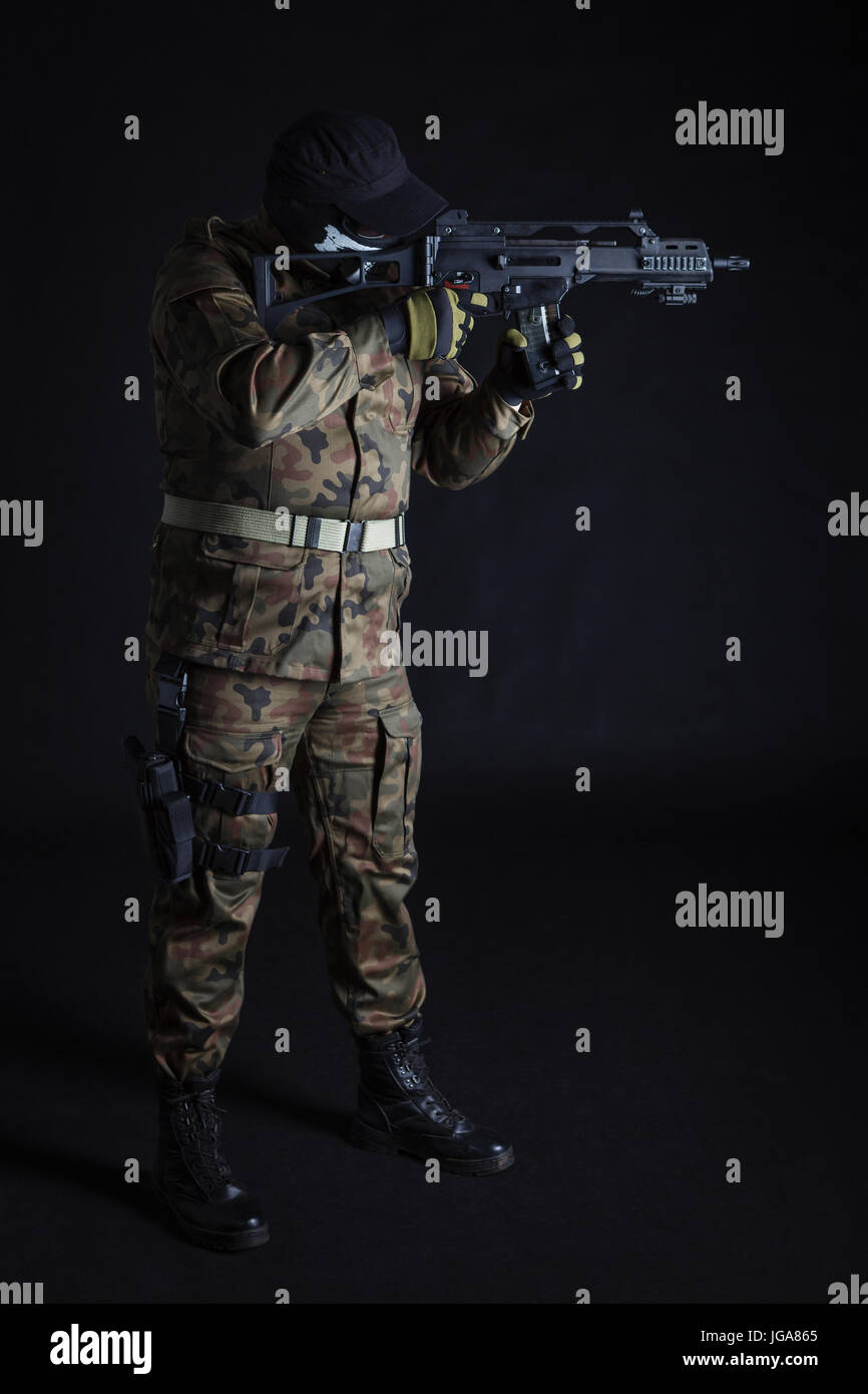 Anti terrorist aiming with a gun on black background - Stock Image