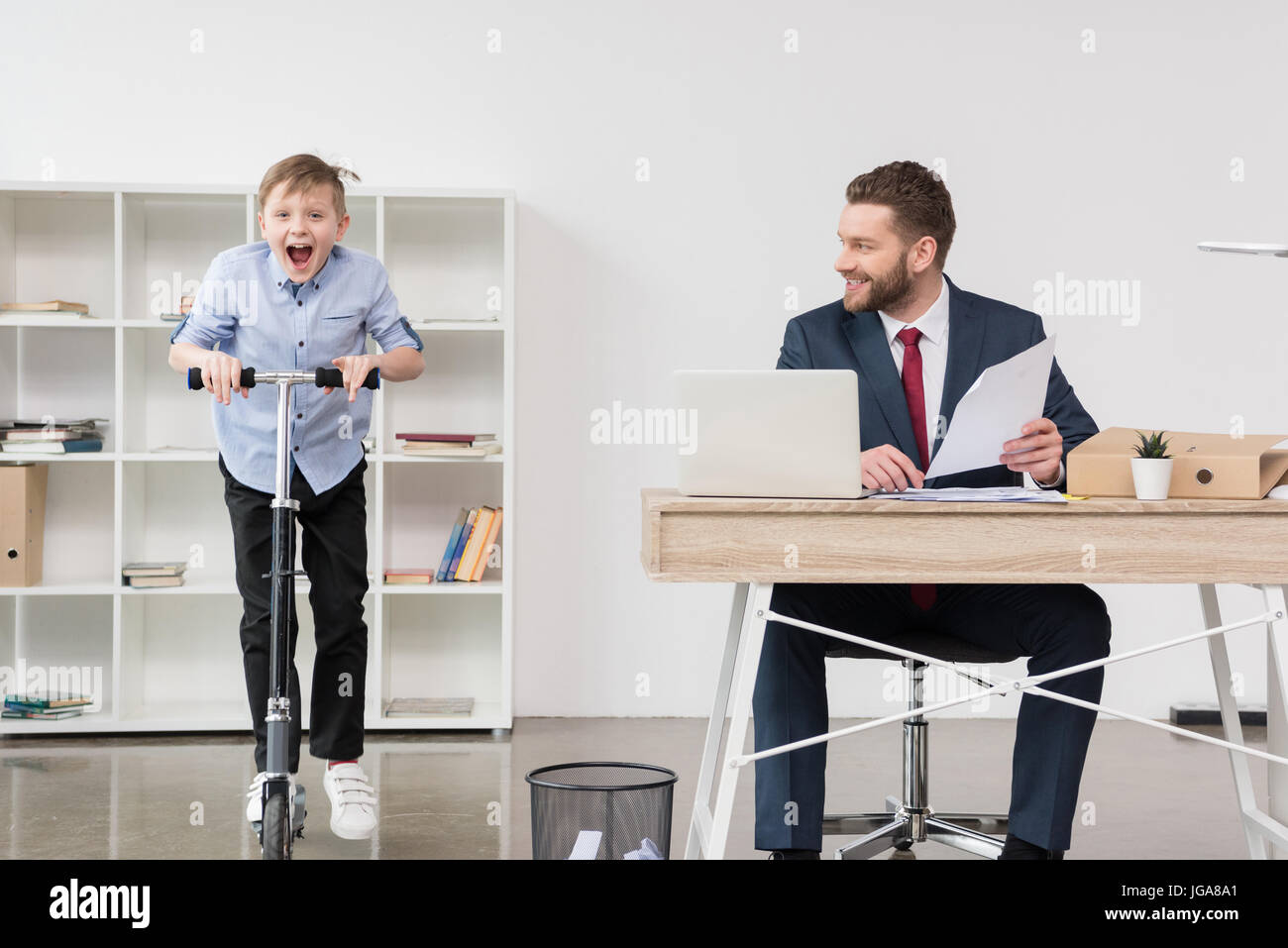 Happy boy riding skooter while his father businessman working at office Stock Photo