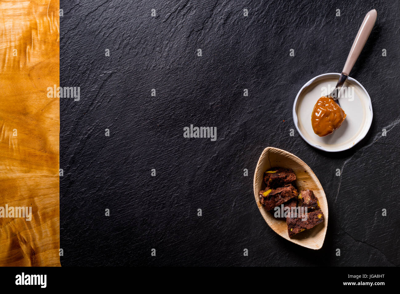 Dulce de leche in a spoon, very sweet creme caramel or praline creme from Argentina,  and some chocolate cookies - Stock Image