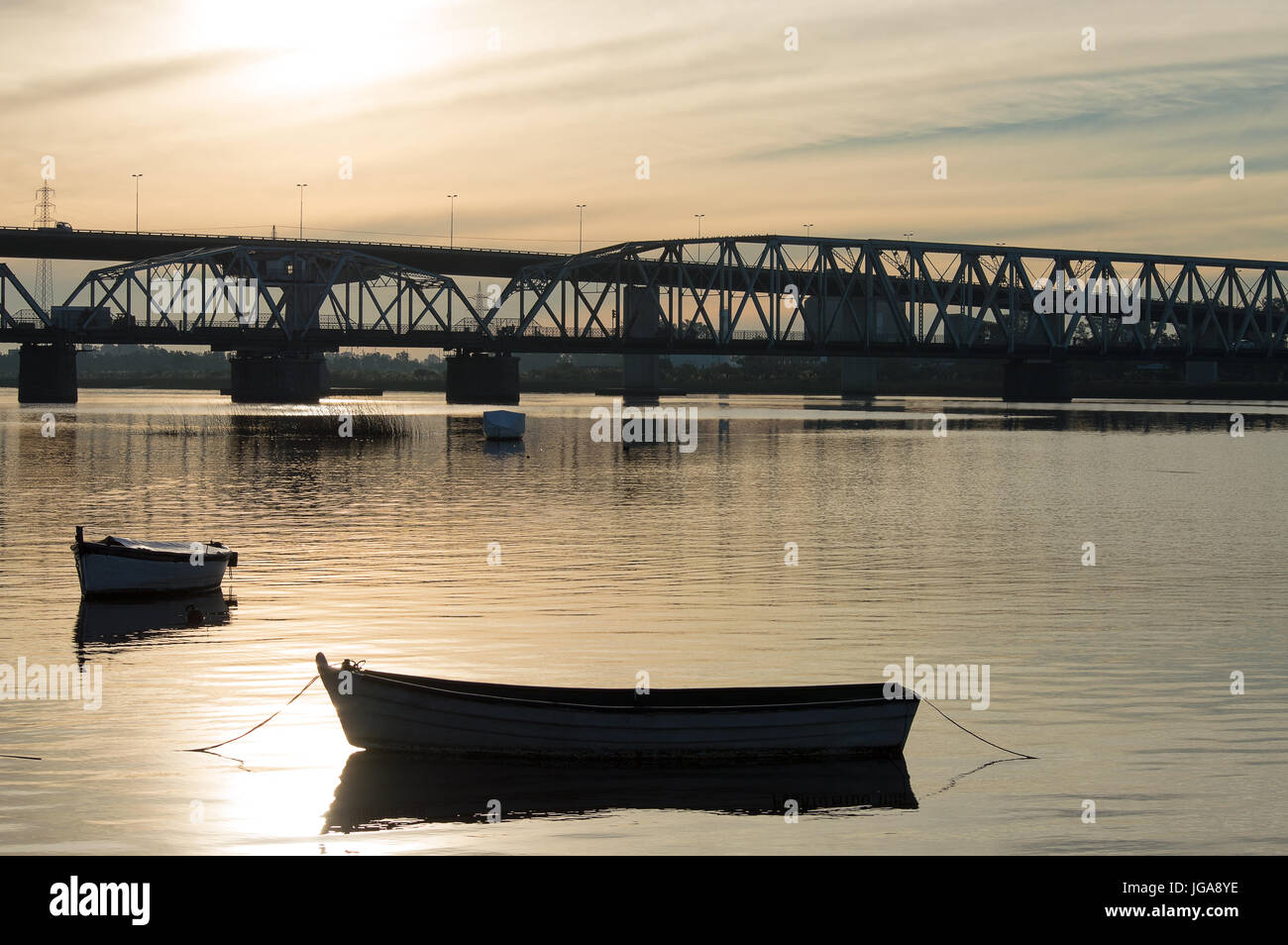 silhouette of the bridge and boats over the Santa Lucia river at sunset in Uruguay Stock Photo