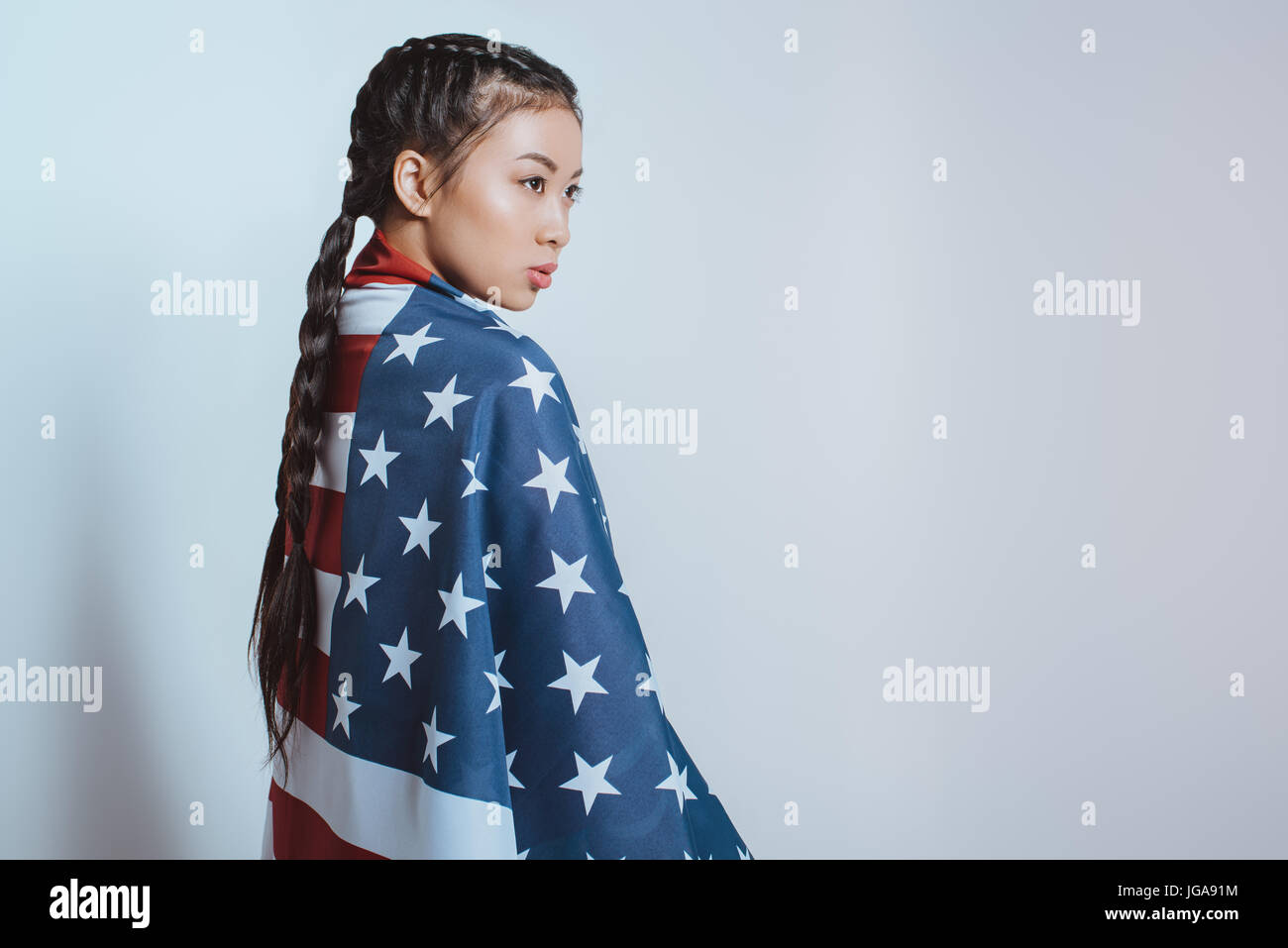 stylish asian girl wrapped in american flag standing and looking away isolated on grey Stock Photo
