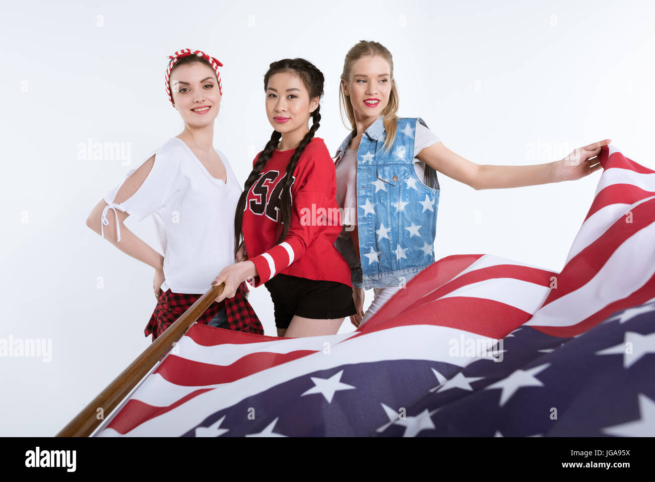 31ea29172cb2e stylish young women posing with american flag in hands isolated on ...
