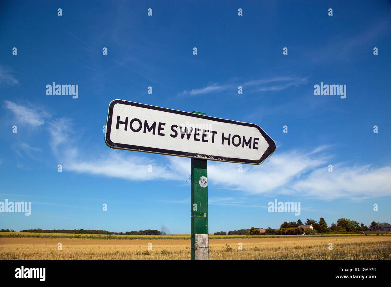 In the countryside a road sign with the inscription  home sweet home, with a blue sky and a field in the background - Stock Image