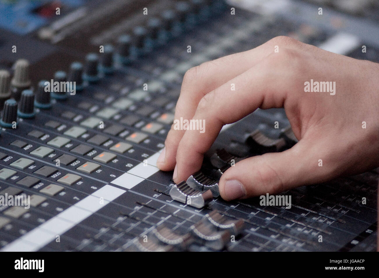 Sound Engineer Operating Professional Sound Mixer at Live Concert, Hand. - Stock Image