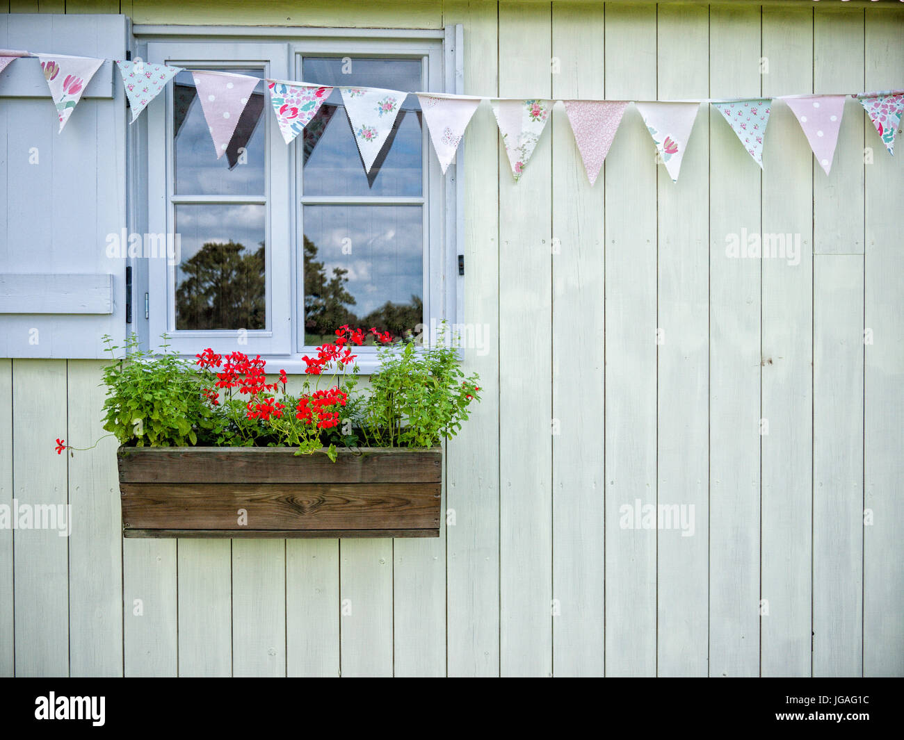 A pretty window on a wooden shed with bunting and flowers in a window box - Stock Image