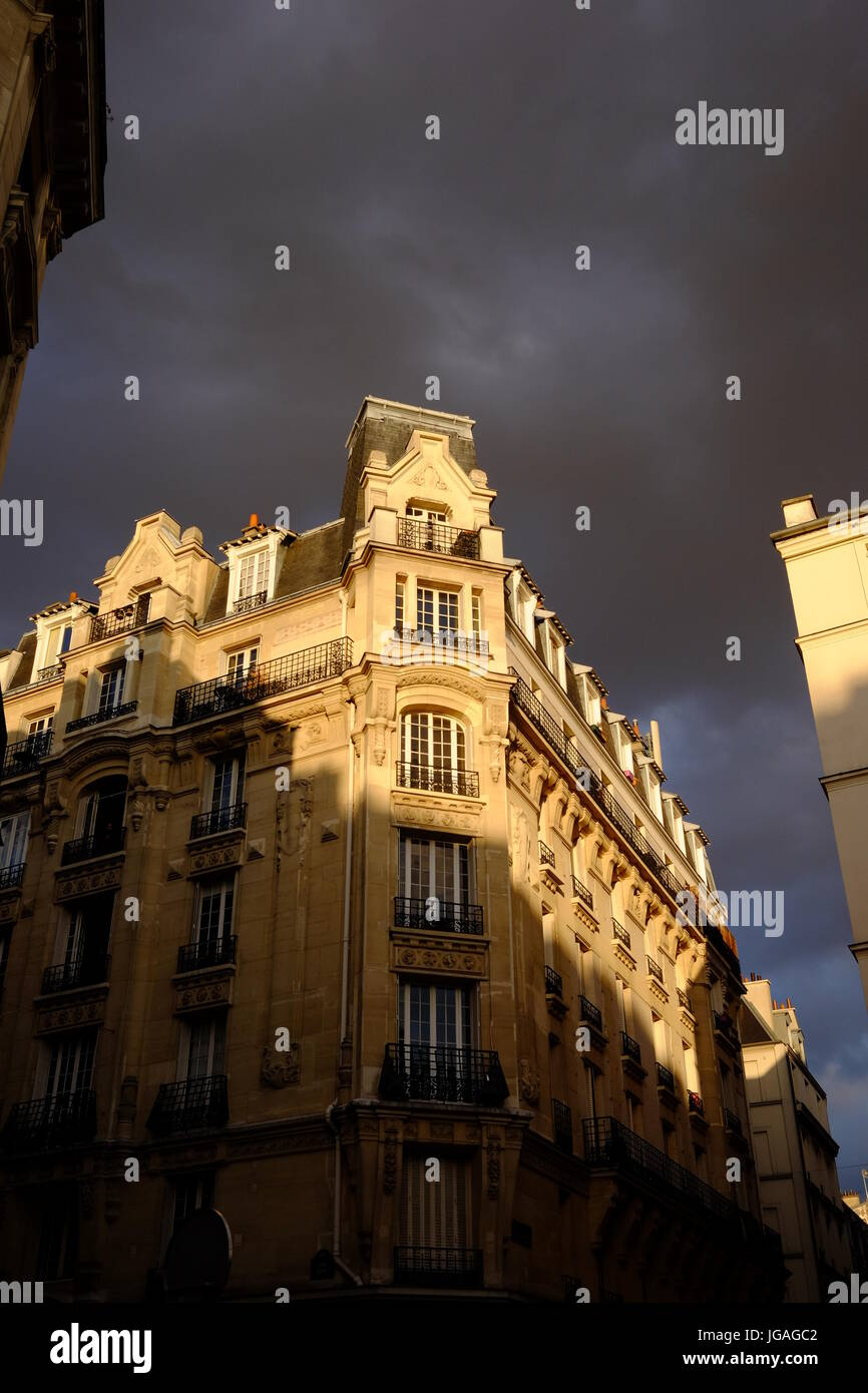 French apartments in Montmartre at sunset with the dark clouds threatening a thunder storm and rain - Stock Image