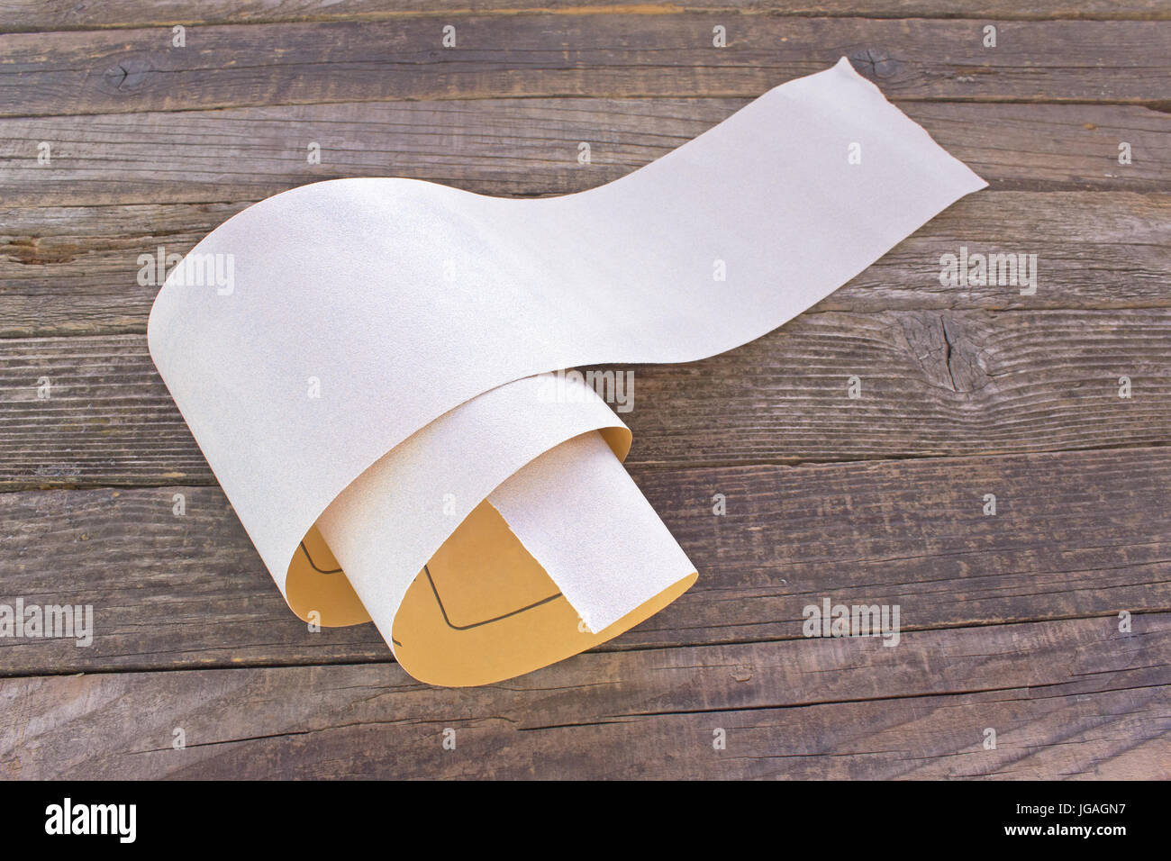 Emery paper - sandpaper on old wooden board - Stock Image