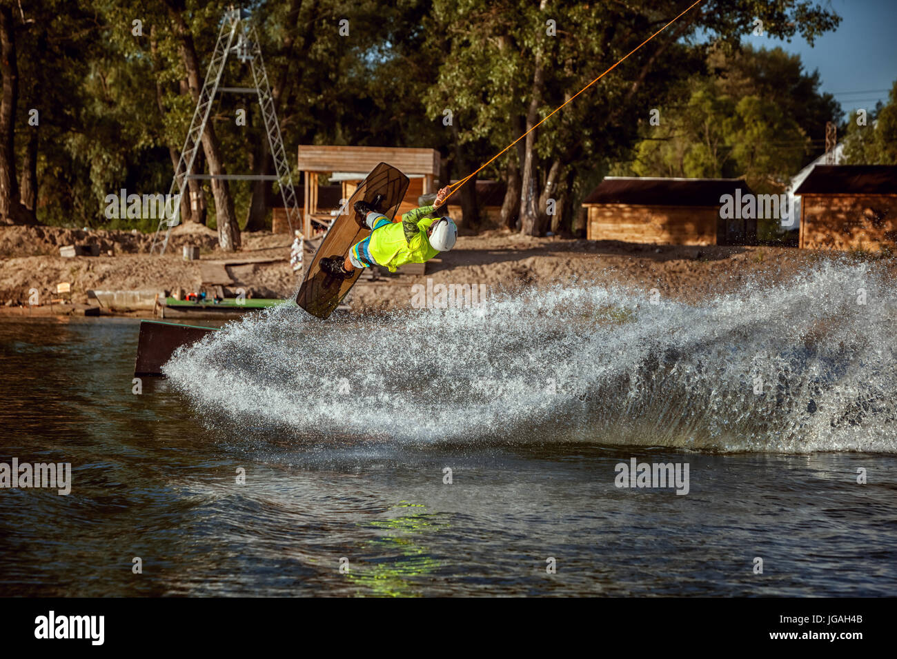 Summer sport wakeboarding. Skating and jumping on the water on the board. - Stock Image