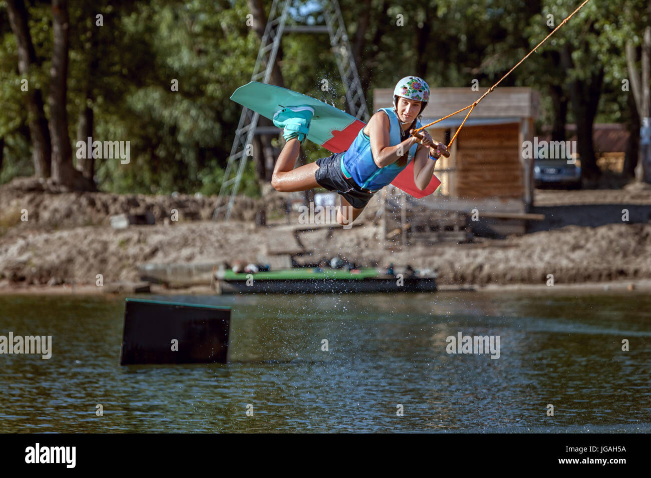 Summer sports wakeboarding, water skiing on the board, jumps and tricks. - Stock Image