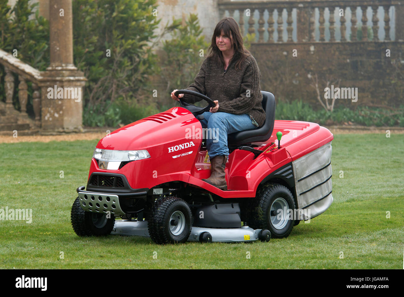 Sit-on mowers being used to cut grass - Stock Image