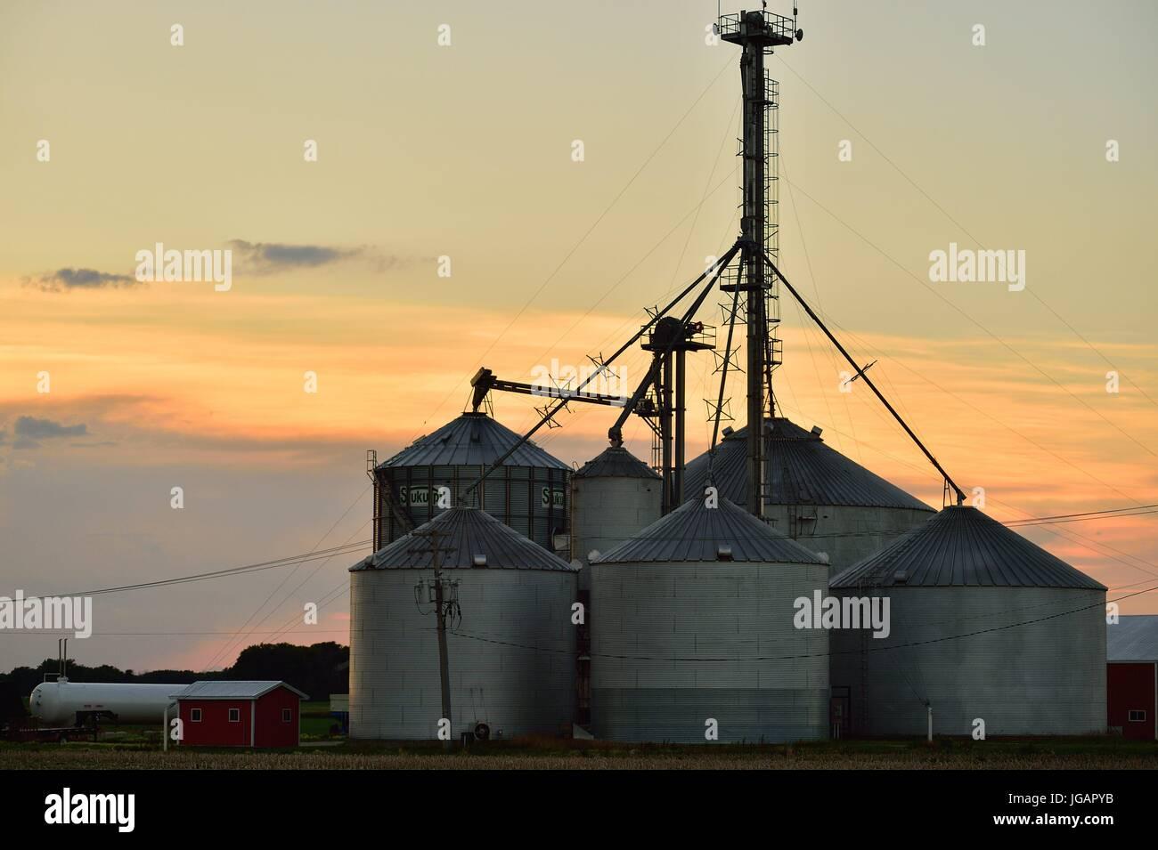 Crop Storage Tanks At A Farm Cooperative Near Burlington, Illinois As The  Sun Sets Beyond A Cloud Bank. Burlington, Illinois, USA.
