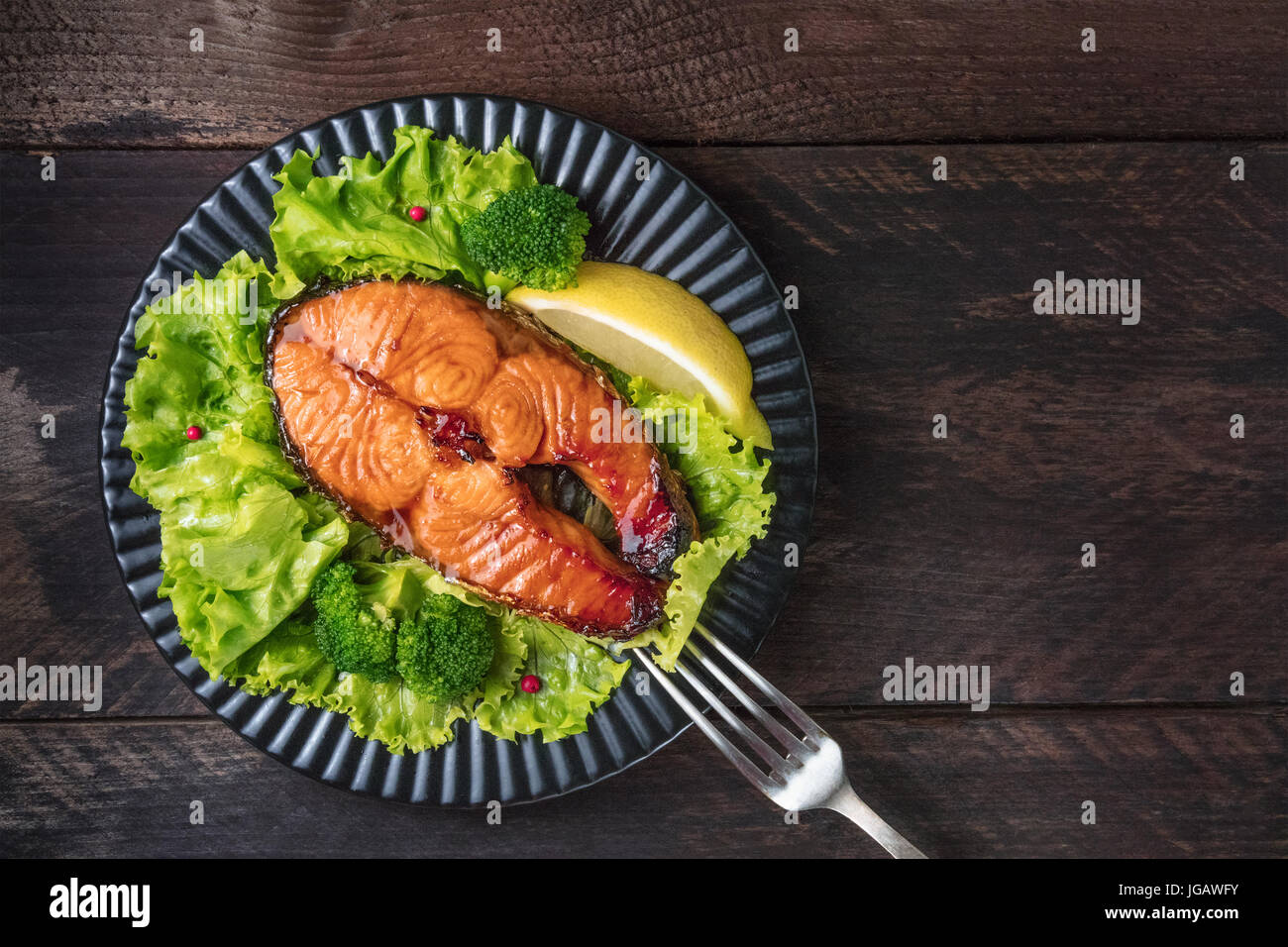 An overhead photo of a grilled salmon steak, with fresh green salad, broccoli sprouts, a slice of lemon, and pink Stock Photo