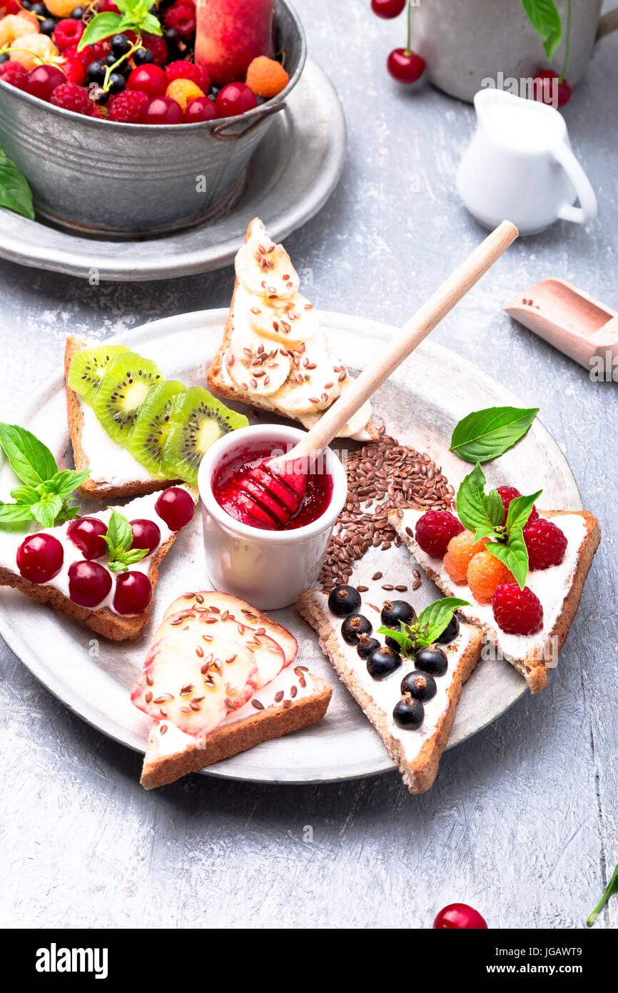 Fruit toast on grey background. Healthy breakfast. Clean eating. Dieting concept. Grain bread slices with cream - Stock Image