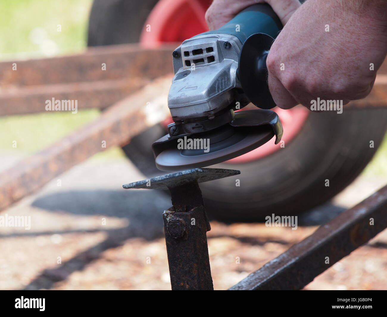 Close up view of an angle grinder being used on a trailer. - Stock Image
