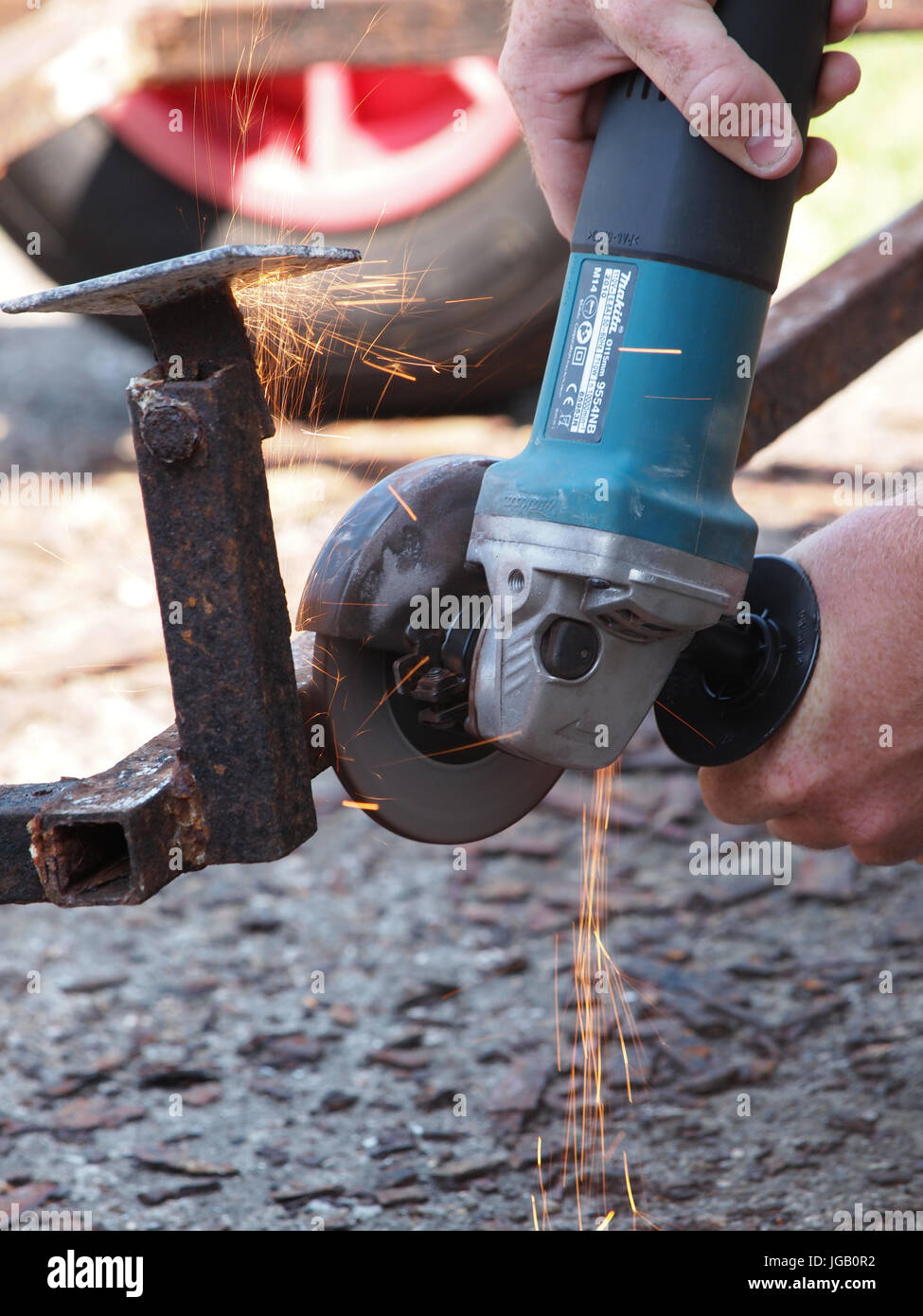 Close up view of an angle grinder being used on a rusty trailer. - Stock Image